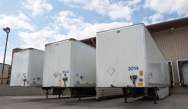 Photograph of Badger Custom Pallet Transport semi trucks docked at the facility.