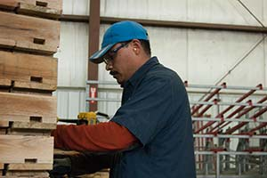 Photograph of an employee inspecting pallets.