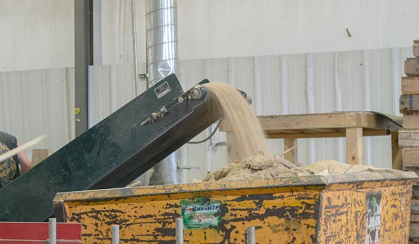 Photograph of pallets being turned into mulch by a wood chipper.