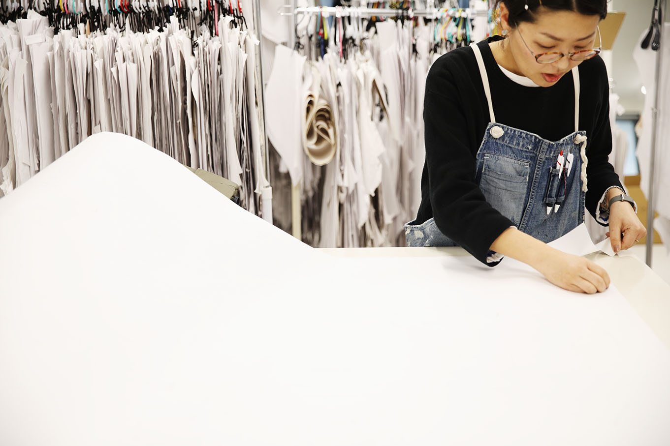 A seamstress at the Japan Blue factory begins the stark white process of denim dyeing.