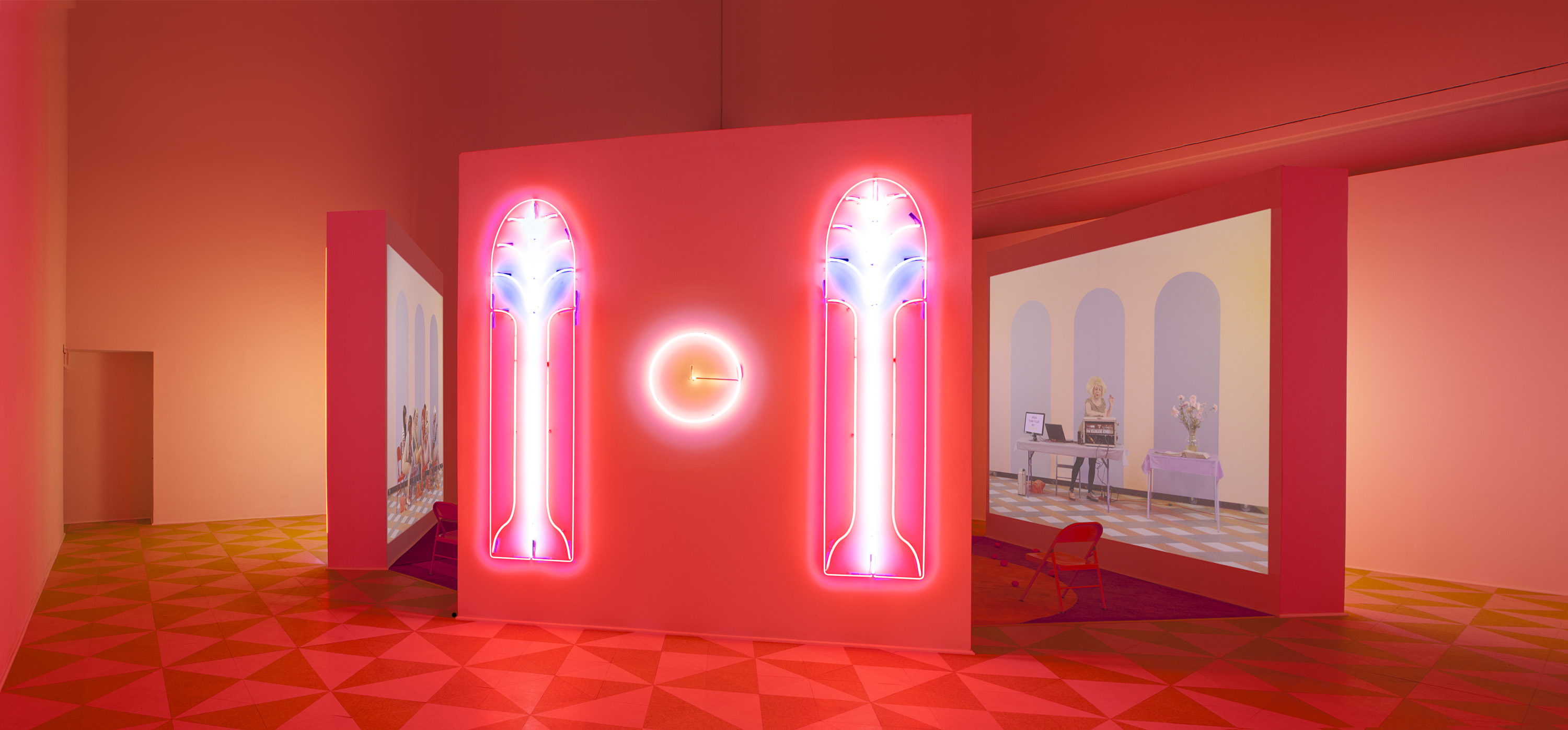 Alex Da Corte (b. 1980) with Jayson Musson (b. 1977), Easternsports, 2014. Four-channel video, color, sound; 152 min., with four screens, neon, carpet, vinyl composition tile, metal folding chairs, artificial oranges, orange scent, and diffusers. Score by Devonté Hynes. Collection of the artists; courtesy David Risley Gallery, Copenhagen, and Salon 94, New York. Installation view, Institute of Contemporary Art, University of Pennsylvania, 2014 © Alex Da Corte; image courtesy the artist and Institute of Contemporary Art, University of Pennsylvania