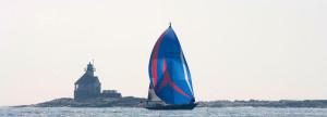 Goshawk ocean racer against lighthouse on Maine coast, Brooklin Boat Yard
