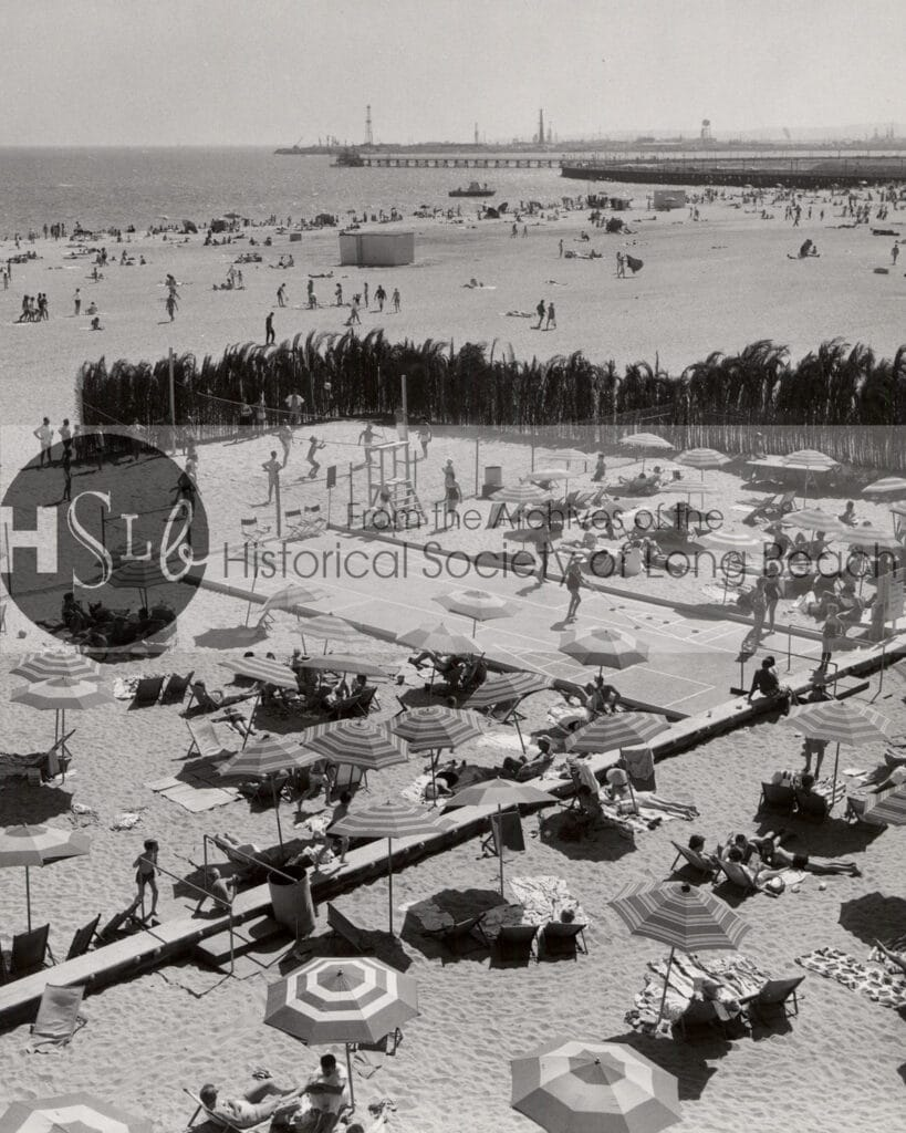 Sunbathers on the beach at the Pacific Coast Club, c. 1960