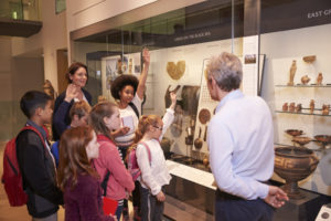 Students Looking At Artifacts In Case On Trip To Museum