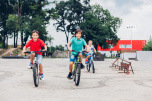 young boys riding their bikes in the skatepark without supervision having fun