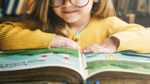 cute smiling girl reading a book in a library