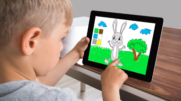 Boy Engrossed In Screen Of Digital Tablet While Playing Game