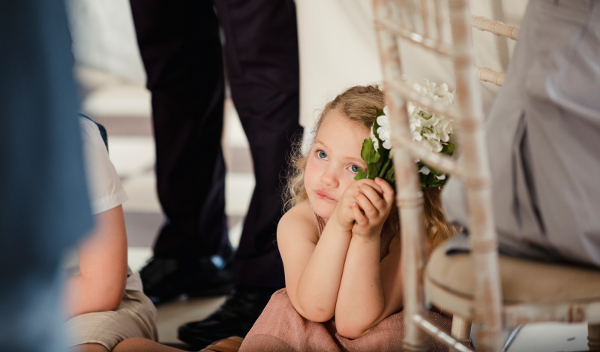 Little girl is sitting on the dancefloor by a table at a wedding. She is watching the bride and groom share their first dance.