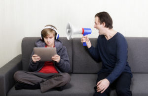 Father using bullhorn to get sons attention while son looks at computer with headphones on
