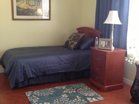 A bedroom in Azalea Gardens resort residence with a cozy single bed by a window, a nightstand with photos. The bed has a blue covering and pillows.