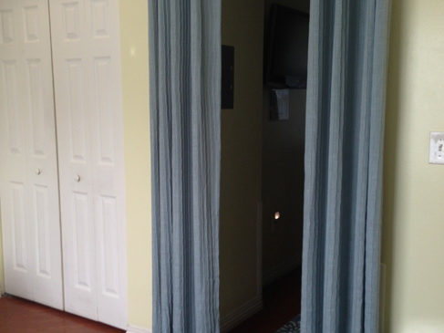 A curtained entranceway and closet doors in a unit in Azalea Gardens.