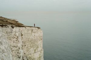 person on a cliff overlooking the water