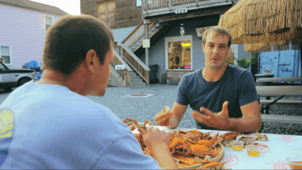 two men eating crabs