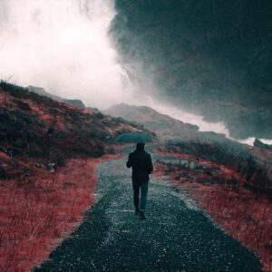 man walking on a path in the rain