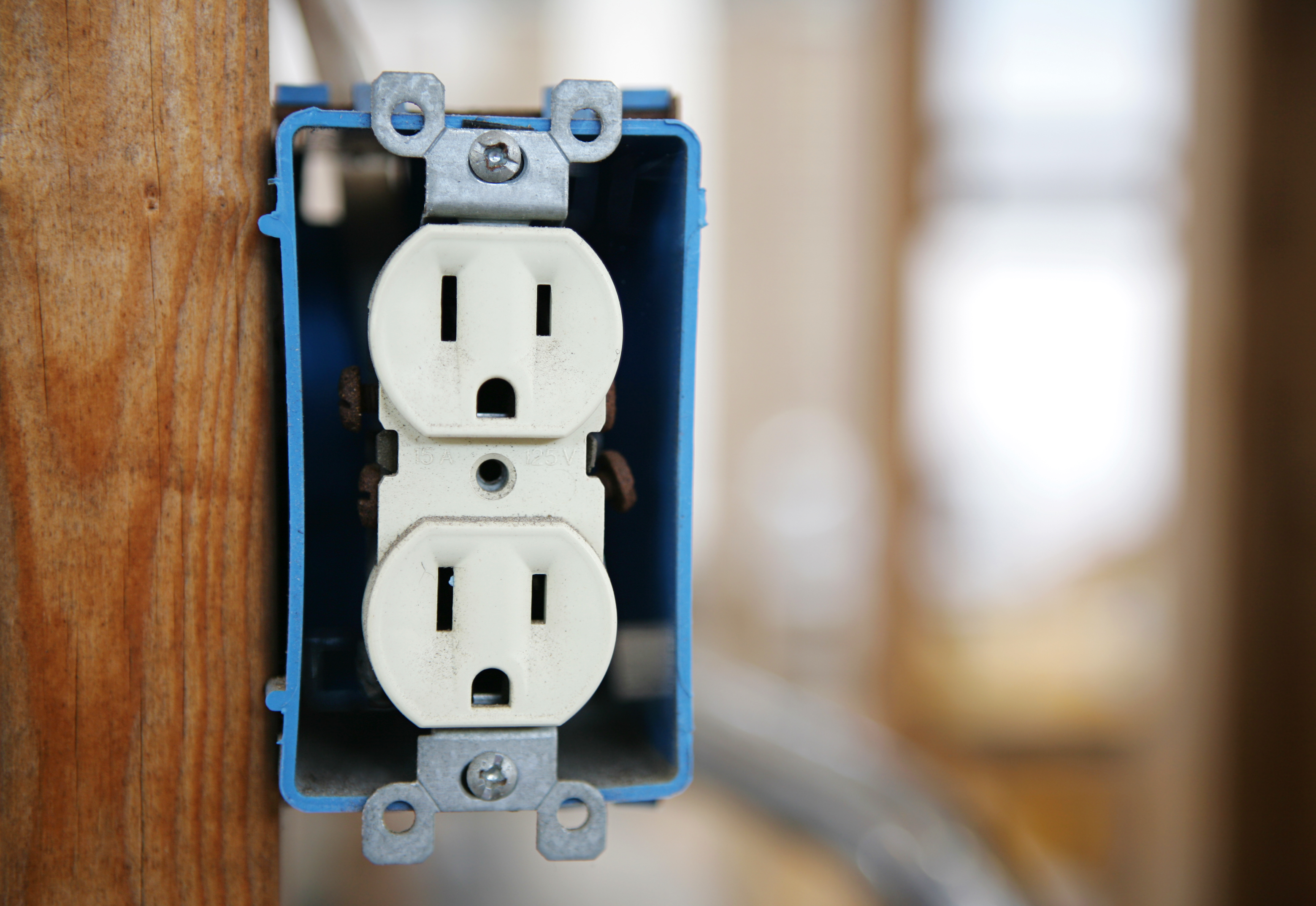 A 120v duplex electrical receptacle box nailed to a wooden stud.