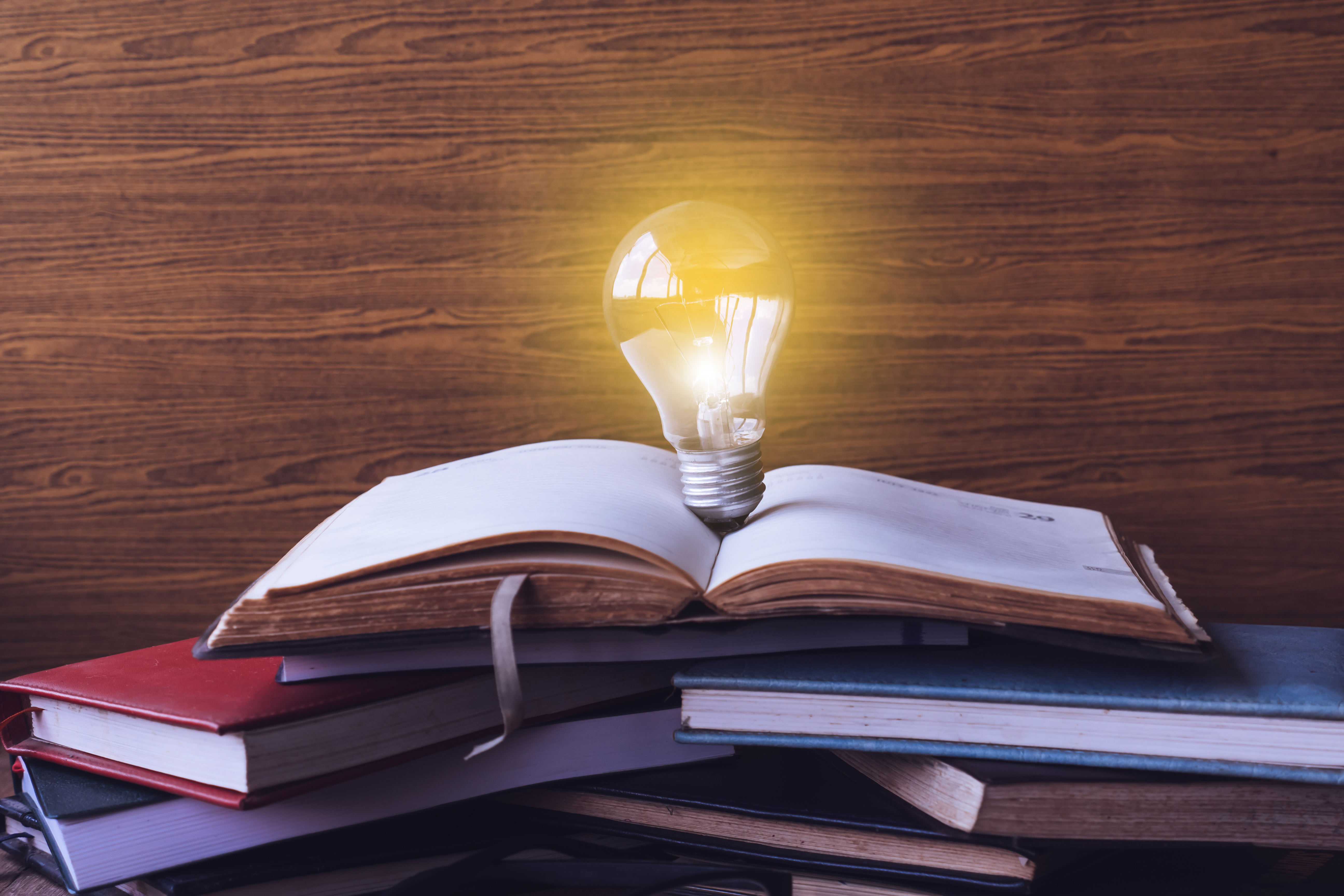 Open book with light bulb and hardback books on wood wall background.