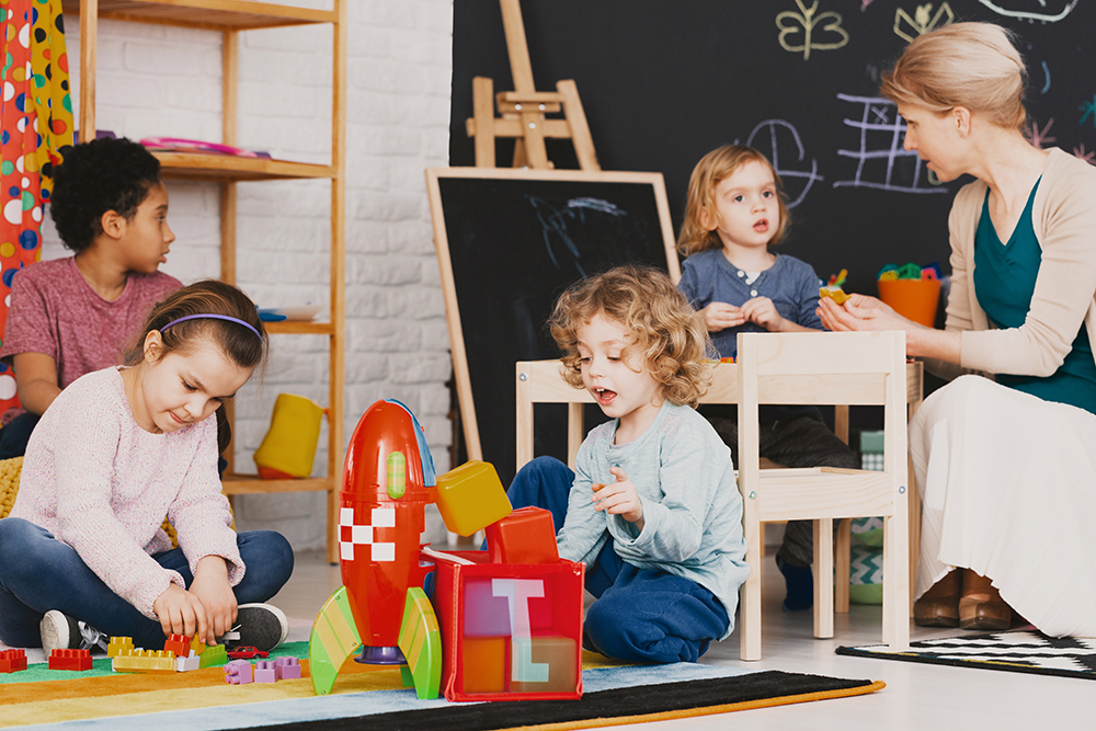 Children playing in a daycare with caregiver.