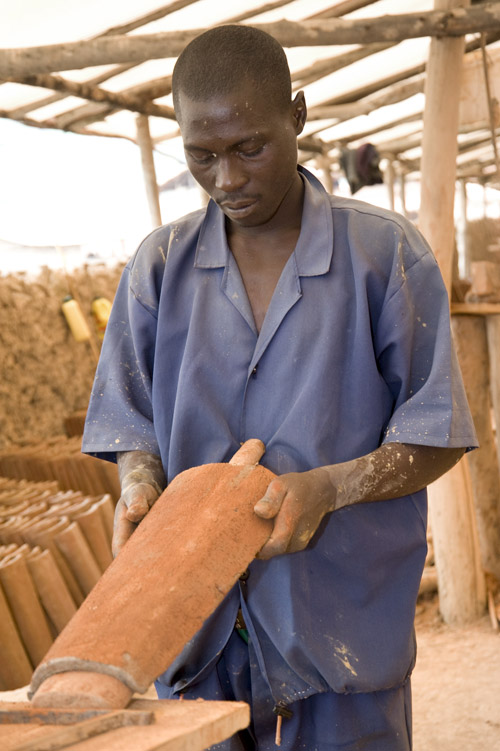 Roofing tiles are shaped around a wooden form, then left for drying.  Later they will be baked in an oven for hardening.