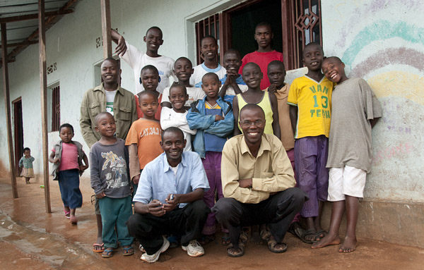 Cofounders and children pose for a photo in front of the orphanage.