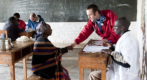 Doctor greeting patient in school house examination room.