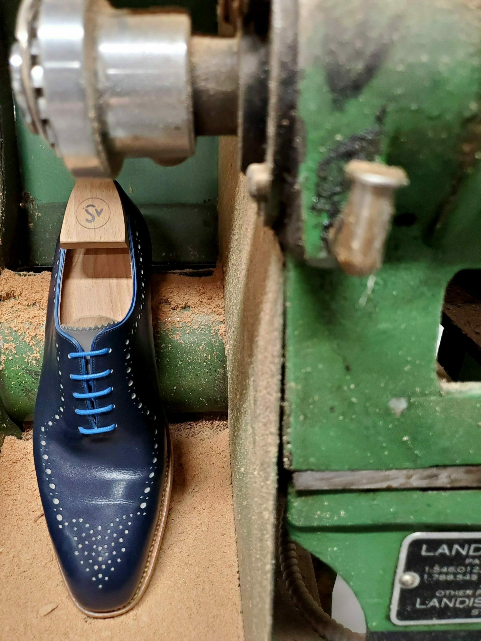 a blue bespoke shoe on a machine