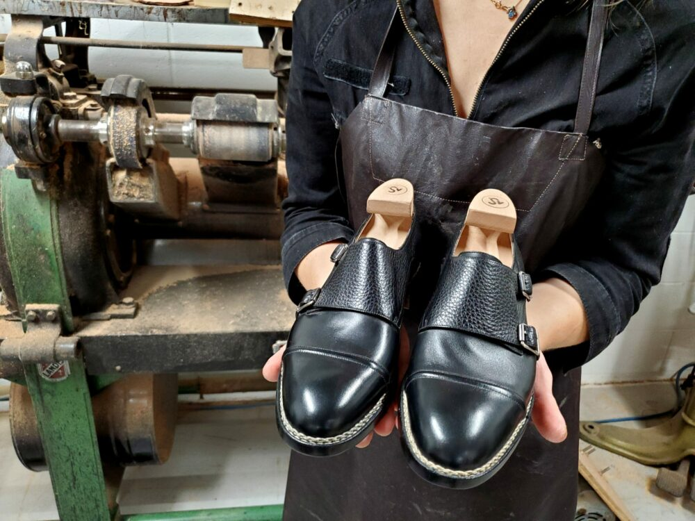 woman holds a pair of amy slosky shoes