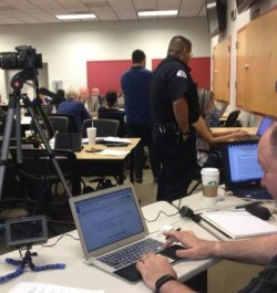 """A PIO360 crisis communications media training, featuring a web-based collaboration space for three """"teams"""" to concurrently work the same scenario, and then test skills via mock news conferences and big screen readouts of press updates and social media messages."""