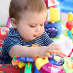 Cute baby with blue eyes playing in his walker