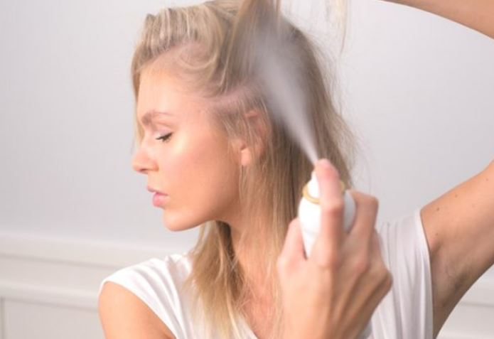 Woman applying dry shampoo to her hair while grinning