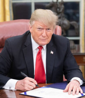 Donald Trump Sitting At Desk Signing Paper