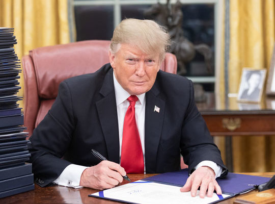 Donald Trump Sitting At Desk Signing Paper