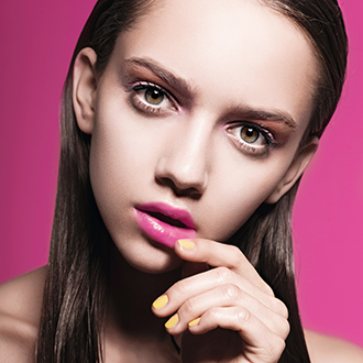 Portrait of a beautiful young girl in the studio on a pink background, beauty concept
