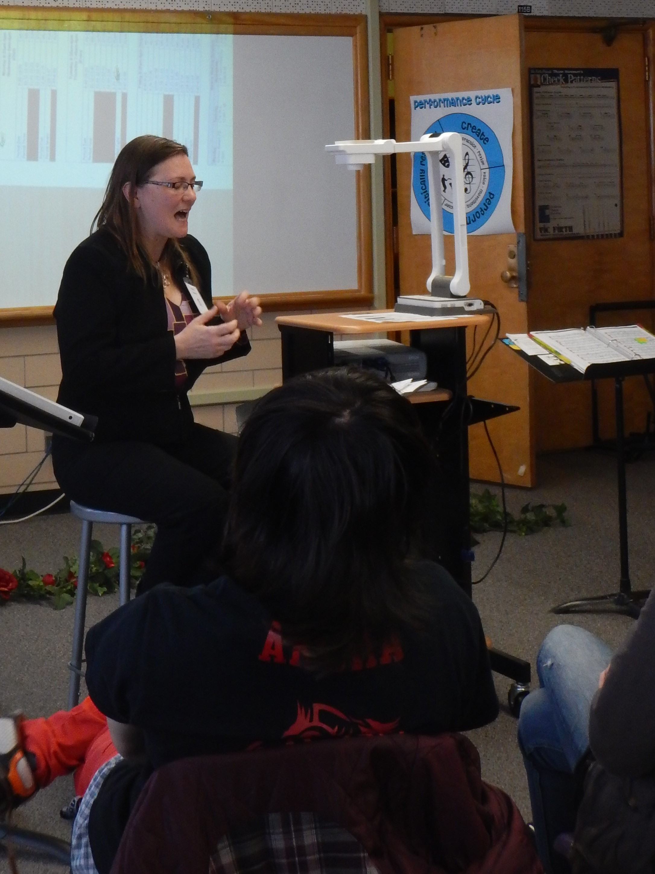 Stage Manager Erin Joy Swank sits near an overhead projector in front of a group of students