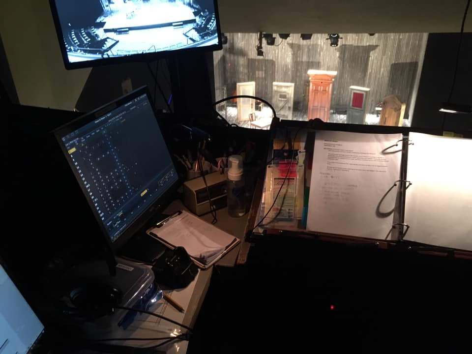 View from the stage manager's booth at Actors' Theatre of Louisville, with script, lighting and infrared monitors, and a view of a stage full of doors.