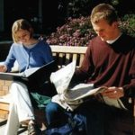 photo of two students reading newspapers on park bench
