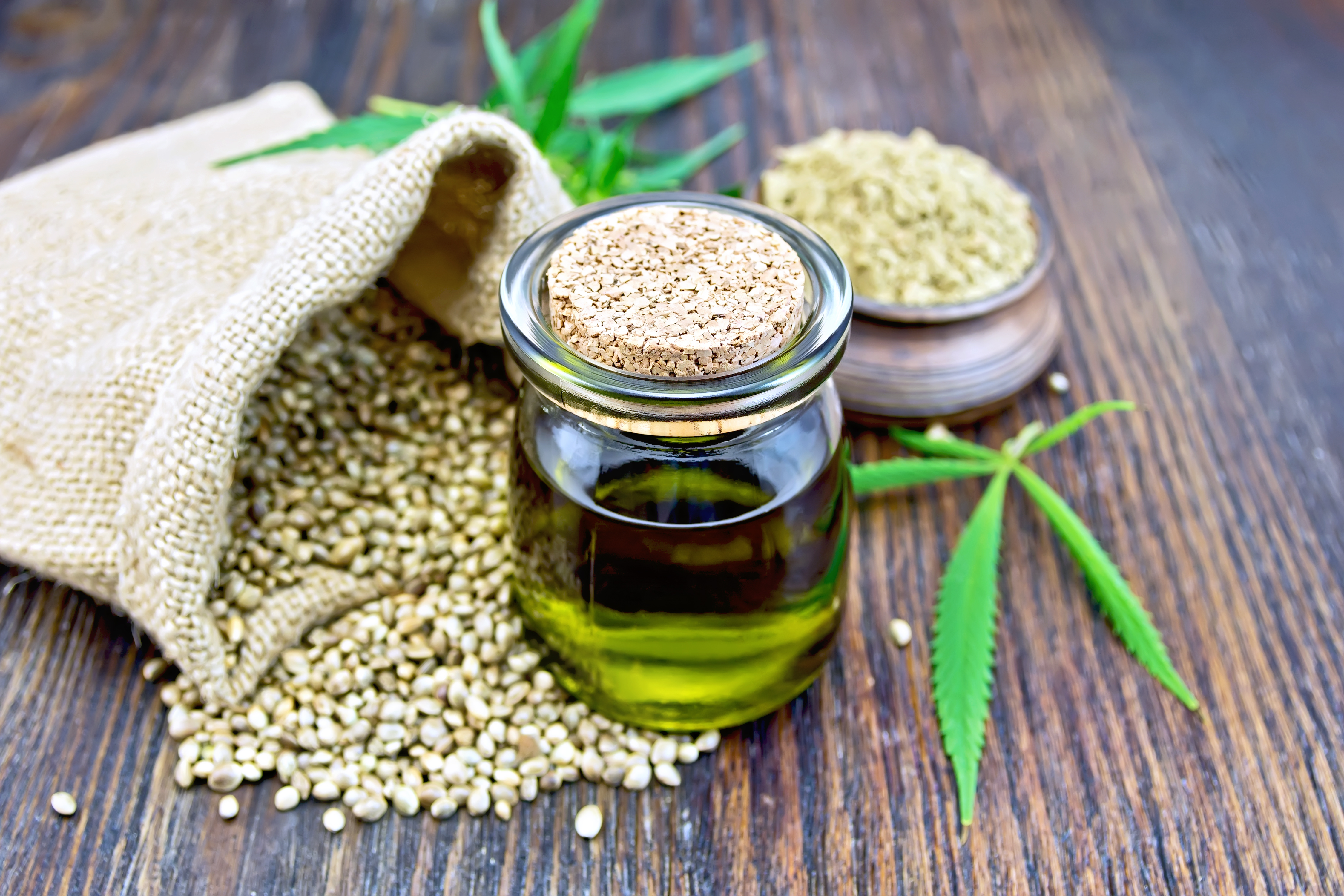 CBD oil sitting in a pile of hemp seeds, which will be used for medicinal purposes