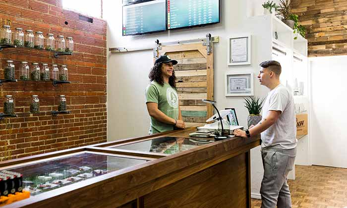 Sage Wellness Dispensary employee helping a customer pick medical marijuana products
