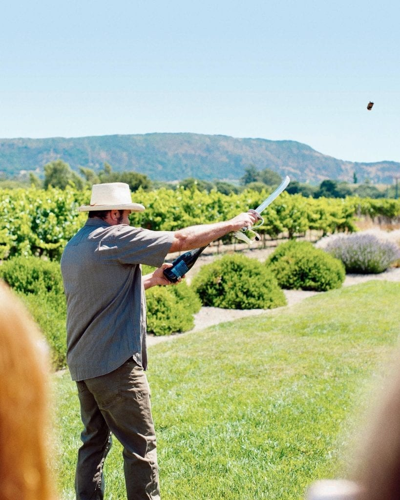 James Hall sabers a bottle of Patz & Hall Brut sparkling wine in Sonoma.