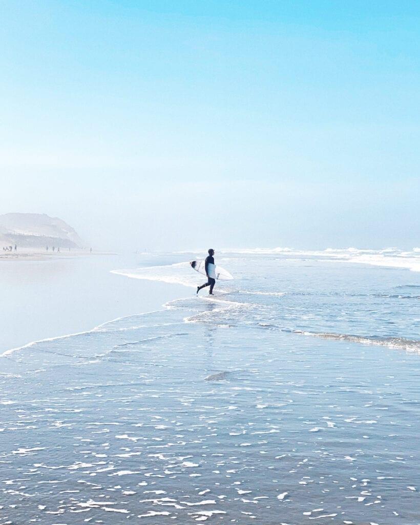 Socially distanced surfer on Ocean Beach during COVID-19 coronavirus lockdown in San Francisco, CA. 49 Miles.