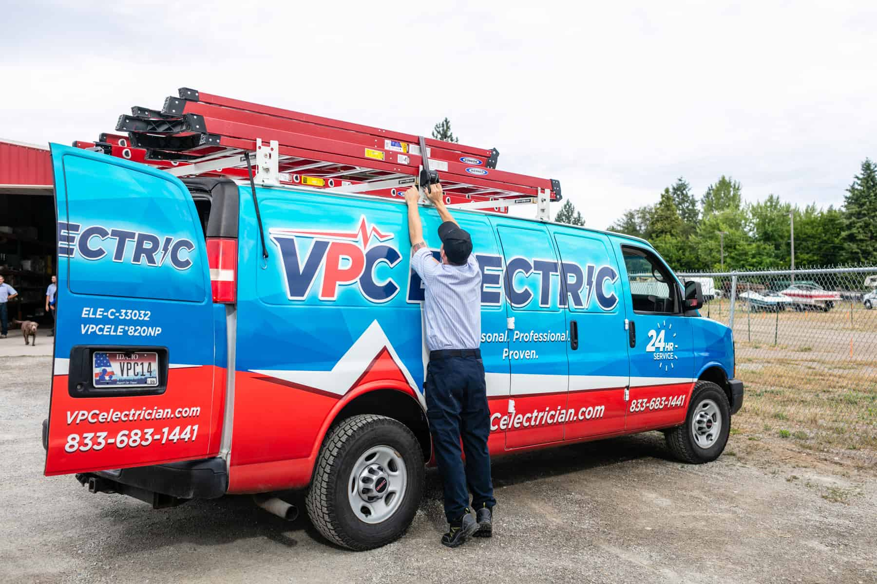 residential electrician loading a ladder onto a VPC electric service van