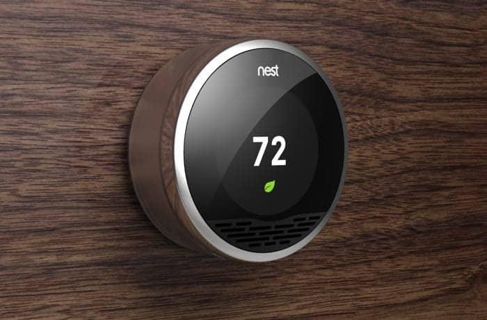 Nest thermostat on a wooden wall programed to a temperature of 72