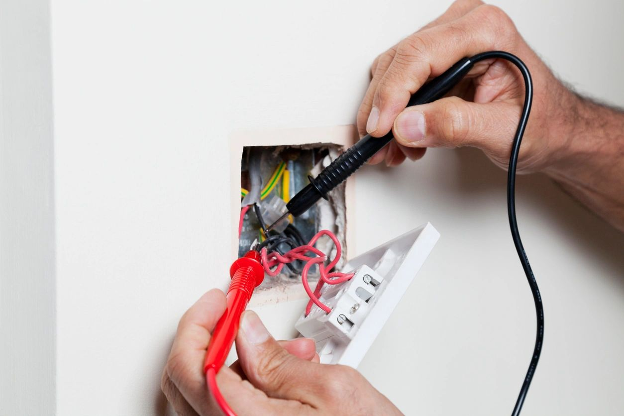 An electrician replacing a GFCI outlet.