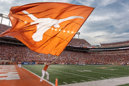 Person Running Flag Across Texas Stadium