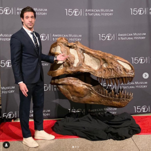 Dustin standing with dinosaur skull