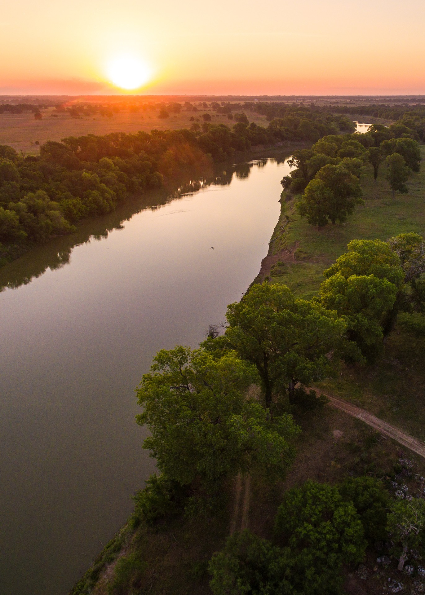 aerial view of sun setting over green pastures and calm river