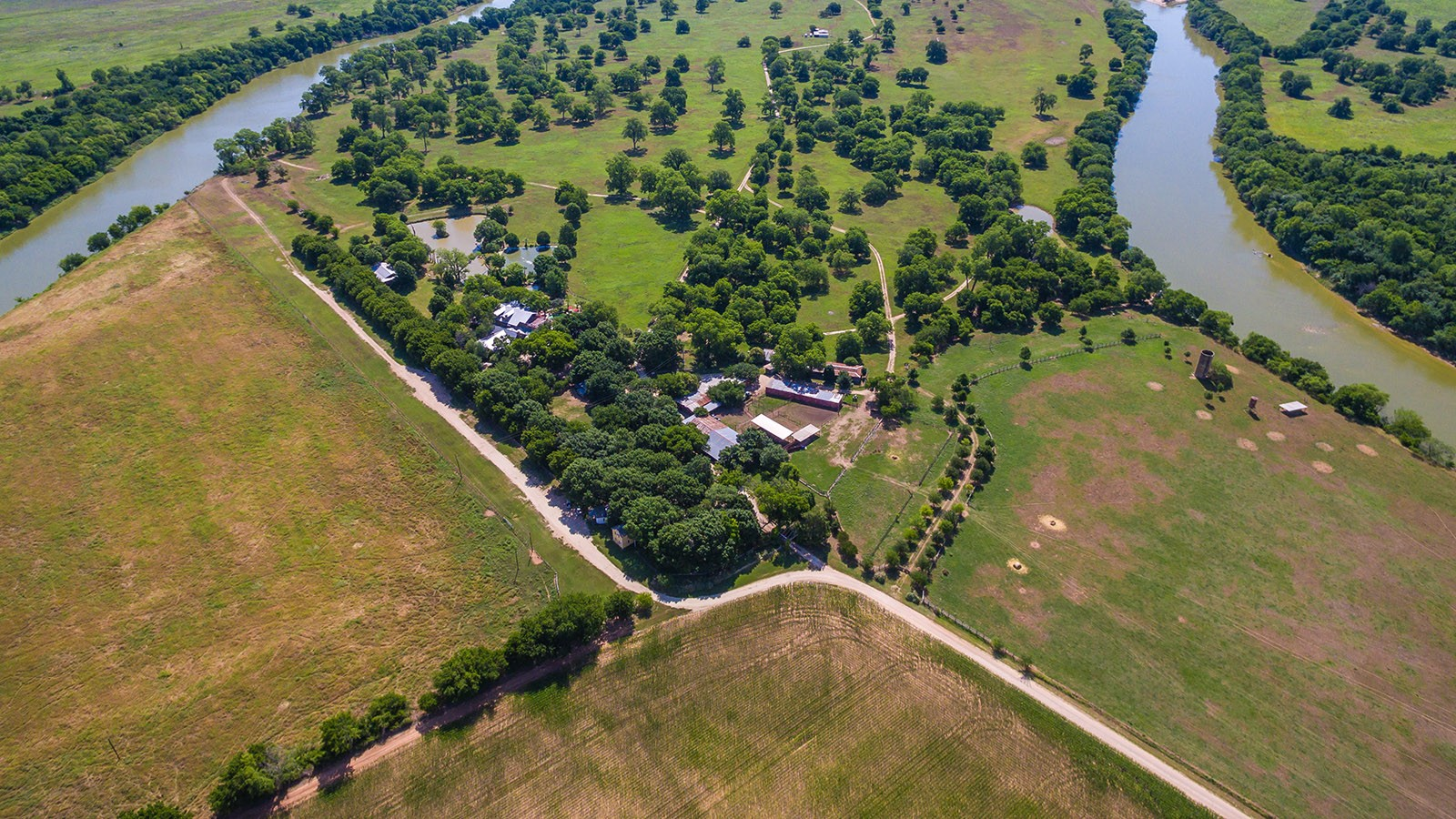 aerial view of main ranch area with grassy pasture and river