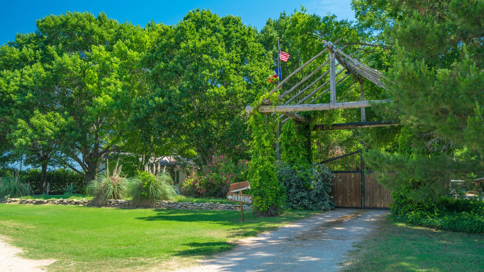 main ranch gate with green trees and buildings
