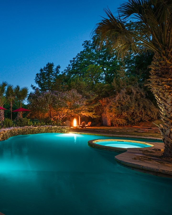 pool area at night with chairs around a fire pit