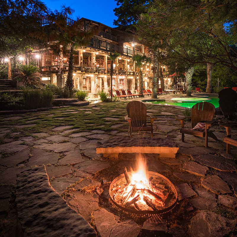 fire pit surrounded by chairs in front of main house at night