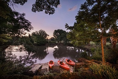 calm lake with orange kayaks during sunset